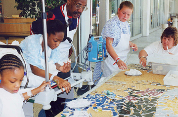 Pediatric hospital patients and community members of differing backgrounds and abilities work together to create a mosaic.